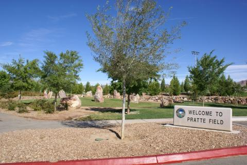 Blue skies, green grass and rocks and trees decorate the open area near the welcome sign for Veteran