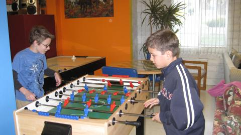 2 boys spar each other in a game of fuseball at the Youth Center.