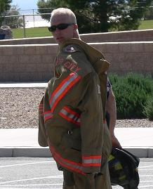 A fireman carrying his uniform coat