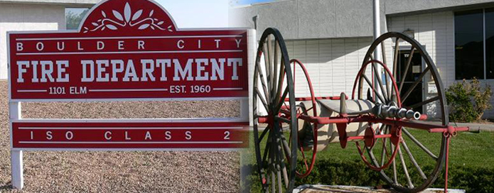 An antique fire hose apparatus next to the Boulder City Fire Department sign
